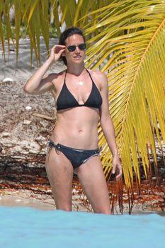 Дженнифер Коннелли в черном бикини на пляже фото #2
